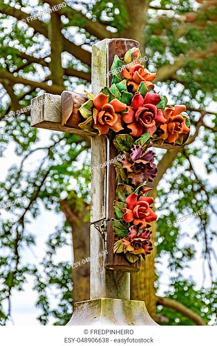Old stone crucifix adorned with flowers in historical cemetery attached to one of the famous churches of the city of Ouro Preto in Minas Gerais, Brazil