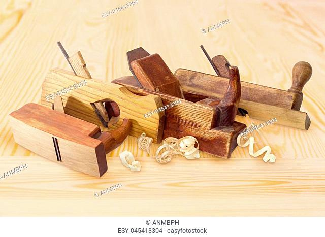 Several old wooden hand planes different special purposes and shavings on a light colored wooden curface