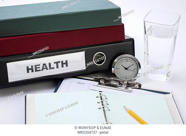 Diary open on a medical chart with a watch and some files next to a glass of water