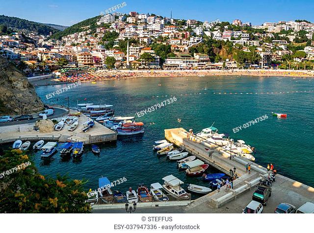 Fishing boats harbor and city beach of Ulcinj. Colorful italian boat at anchor. View from ancient fortress walls. Ulcinj, Montenegro
