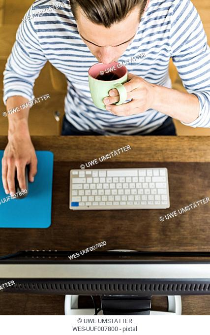 Man using computer and drinking coffee from cup at desk