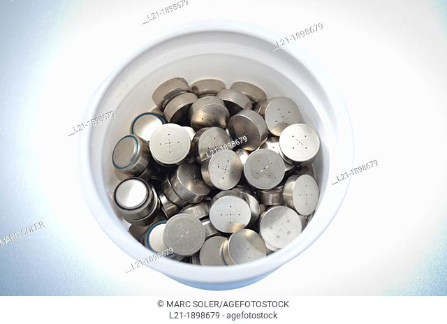 Button batteries for recycling in a white plastic container
