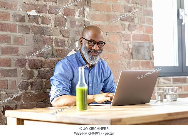 Portrait of laughing businessman working on laptop