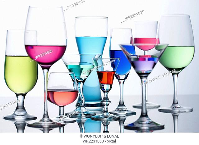 Different types of glasses for drink with colorful liquid in each