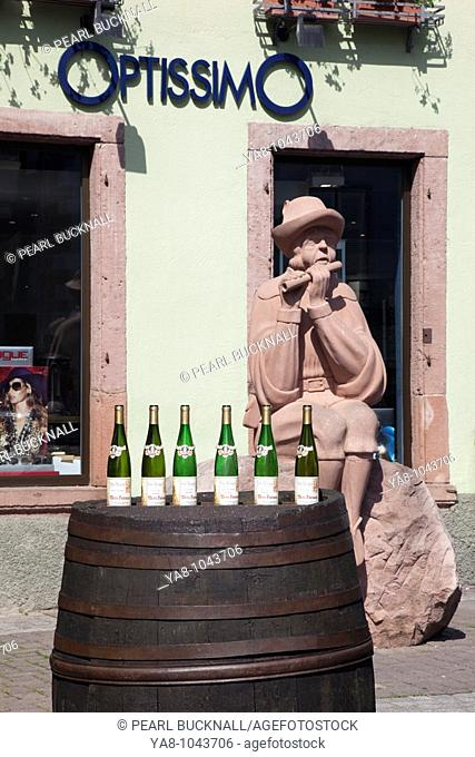 Ribeauville, Alsace, Haut-Rhin, France, Europe  Display of wine bottles on an old wooden barrel beside a statue in town on Alsatian wine route