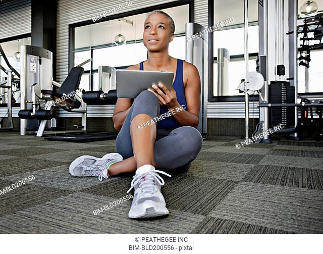 African American woman using digital tablet in health club