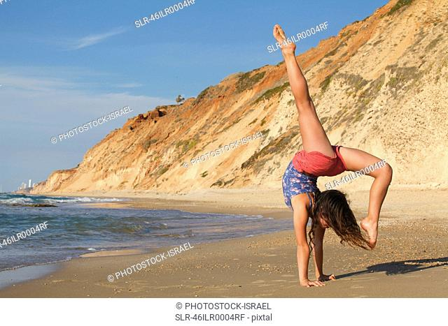 Woman doing gymnastics on beach