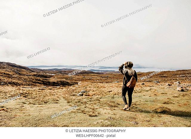 UK, Scotland, Highland, Applecross, rear view of young woman in rural landscape