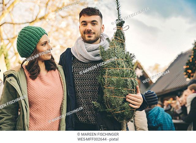 Happy couple with a tree on the Christmas Market