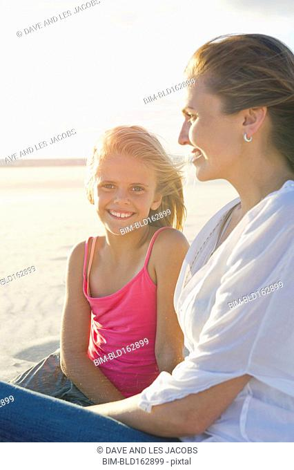 Caucasian mother and daughter sitting on beach