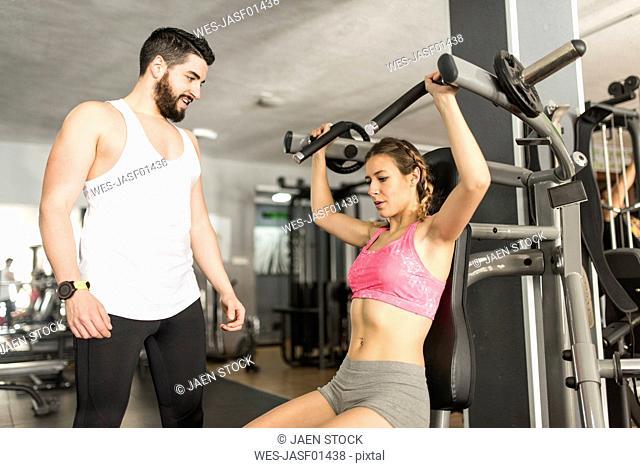 Coach training woman in gym