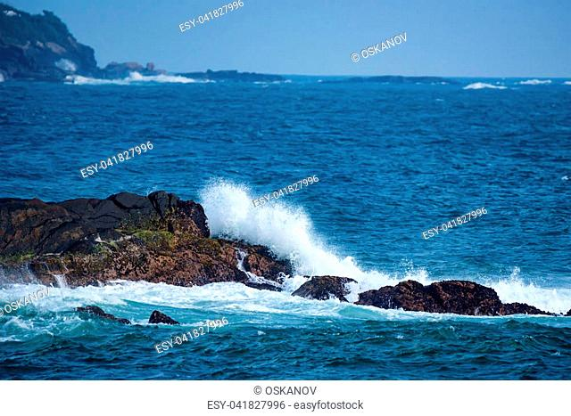 Waves spashing against the rocks and reef near the sea shore. Littoral or breaker zone