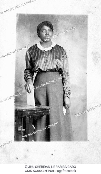 Three quarter length portrait of African American woman, with a blank facial expression, wearing a dark dress, standing behind a table as she holds a white book...