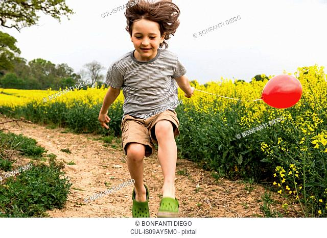 Boy jumping on yellow flower field track pulling red balloon