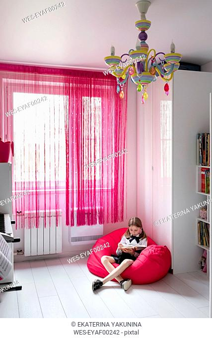 Girl reading a book in her room