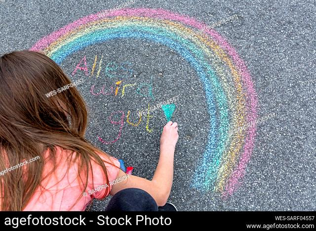 Girl painting rainbow on street with text 'Everything will fall into place'
