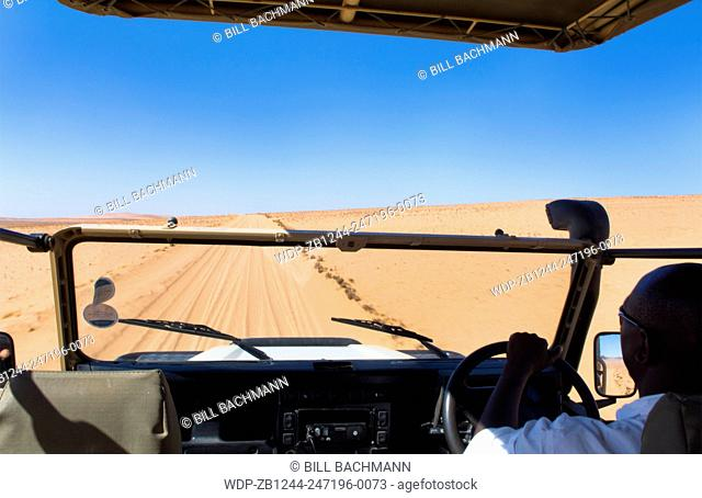 Namibia Northern Desert of Namib Desert riding safari vehicle in sand dunes of Hartmann Berge deserted land Hartmann Valley Marienflub with hills and ripples
