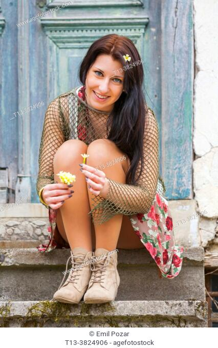 Countrygirl sitting on steps with flowers in hand