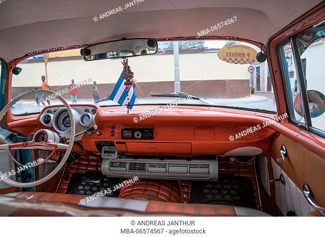 Vintage car taxi from the inside with Cuban flag, Havana, Cuba