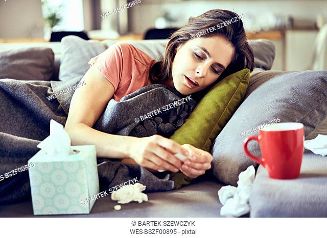 Portrait of sick young woman lying on covered in blanket trying to take pills for cold