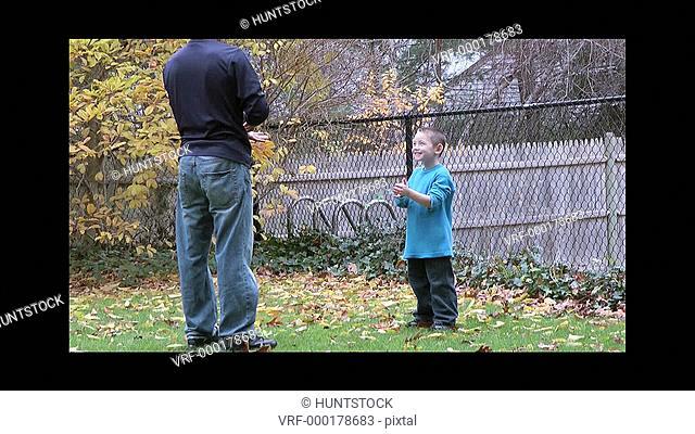 Family raking front yard communicating using American Sign Language saying: Raking leaves