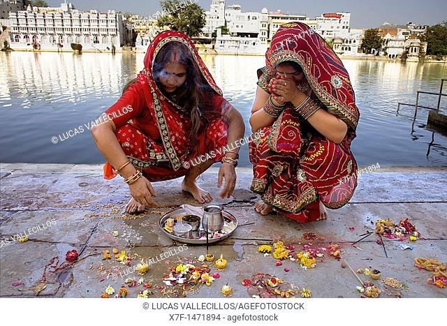 Girls praying, making a offering,in Gangaur ghat,Pichola lake,Udaipur, Rajasthan, india