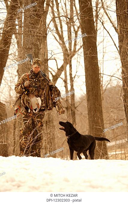 Hunter In Snow With Black Lab