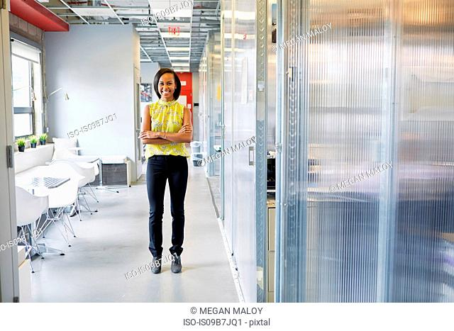 Portrait of young woman in office environment, arms folded, smiling