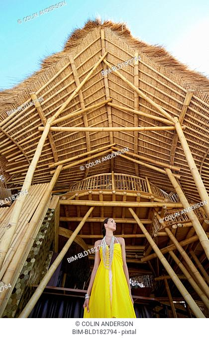 Pacific Islander woman standing under wooden awning