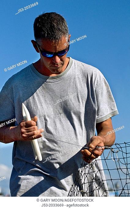 Fisherman repairing fishing trawl net, Anacortes, Washington USA
