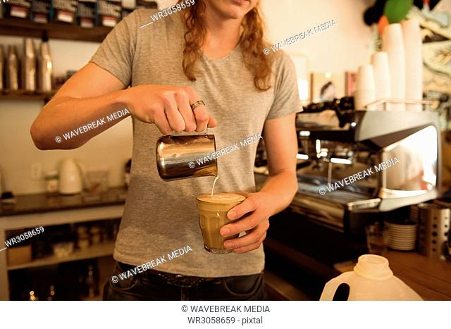 Mid section of barista making coffee