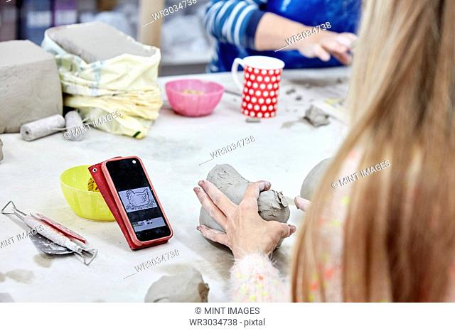 People seated at a workbench in a pottery studio. A woman using a sketch on her phone as reference to model clay