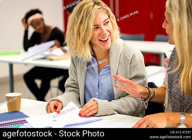 Female community college students talking, studying in classroom