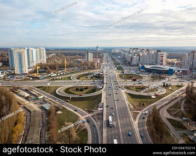 Aerial view of the drone on the Odessa square with highway in the form of a quatrefoil with passing cars and a modern city against a cloudy sky autumn day