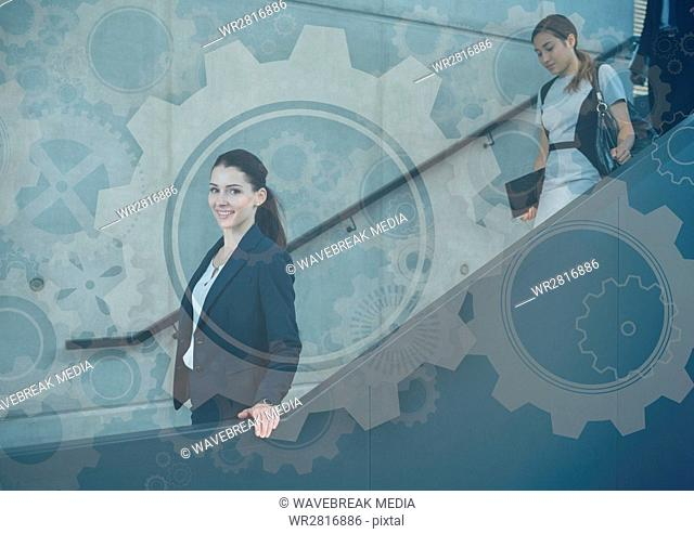 Business people walking down stairs with gear graphics overlay
