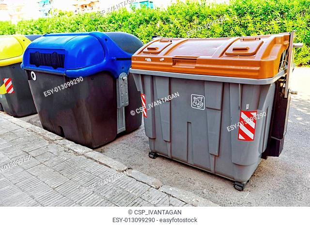 Variety dumpsters(recycling containers ) on a city street