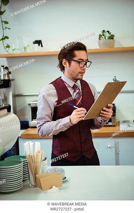 Man writing with pen on clipboard