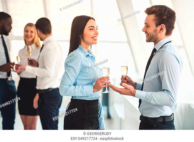 Successful business people are drinking champagne, talking and smiling while celebrating in office