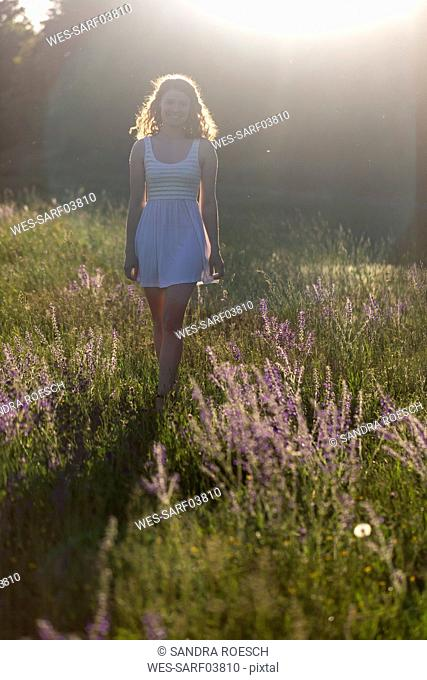 Young woman walking on flower meadow in the evening light