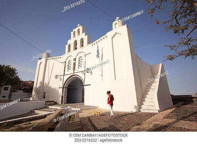 Woman in front of the St. Mary's Church with a two-storey bell tower from 1660, Pyrgos, Santorini, Cyclades Islands, Greek Islands, Greece, Europe