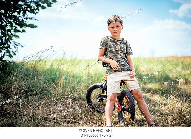 Portrait confident boy on bicycle in rural field