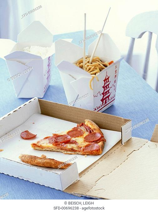 Assorted Take Out Food on a Table, Pizza and Chinese
