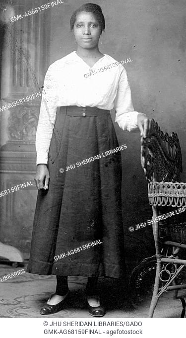 Portrait of an African American woman standing in front of a mural with her left hand resting on the back of a wicker chair, her right arm is by her side