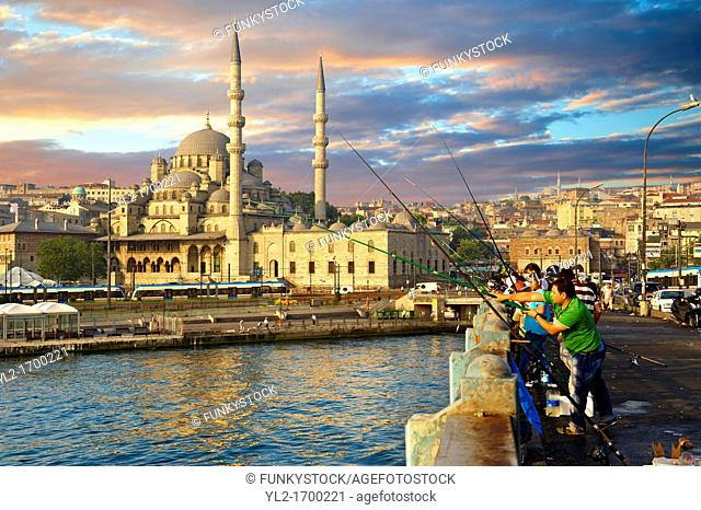 Fisherman on the Galata bridge fishing in the Golden Horn next to The Yeni Camii, The New Mosque or Mosque of the Valide Sultan ordered by Safiye Sultan in 1597