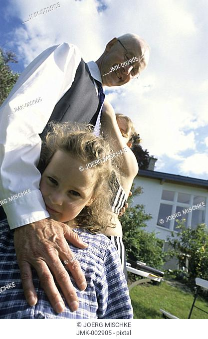 A senior, businessman, father, grandfather, 45-50 50-55 55-60 years old, and two girls, 1-5 5-10 years old, in a summerly garden