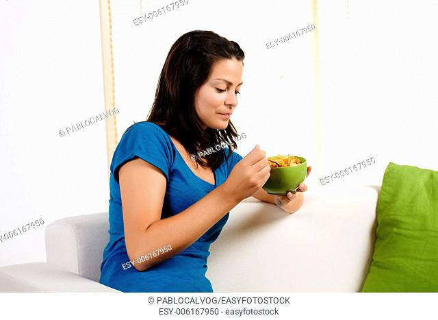 Portrait of a beautiful young woman eating cereal and sitting in a couch