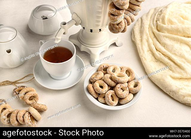 a samovar with bagels and hot tea on the white tablecloth