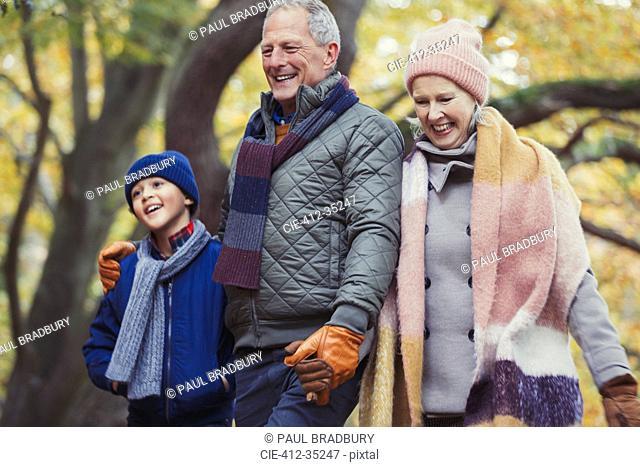 Grandparents walking with grandson in autumn park