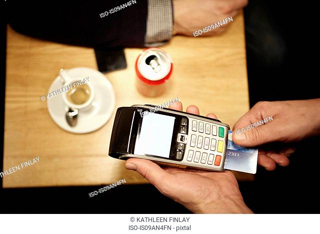 Restaurant worker inserting customer's credit card into credit card reader