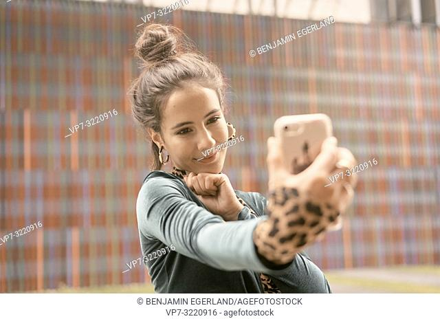 content woman using smartphone, taking selfie, video conversation